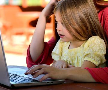Dziewczynka z mamą przegląda komputer